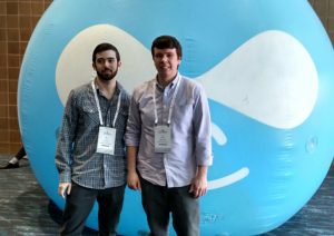 Alex Miner and Len Brashear in frontof the inflatable Drupal logo